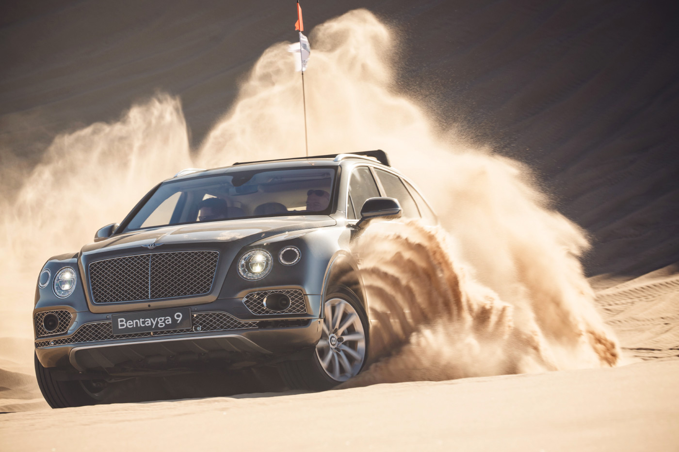 <p>Bentley's Bentayga SUV kicking up the sand in the Glamis Sand Dunes in Southern California.</p>