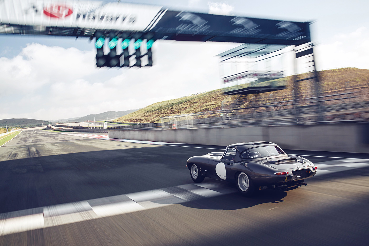 <p>Car number one of the 'missing' Lightweight E-types crosses the finish line at the Navarra Circuit, Spain.</p>